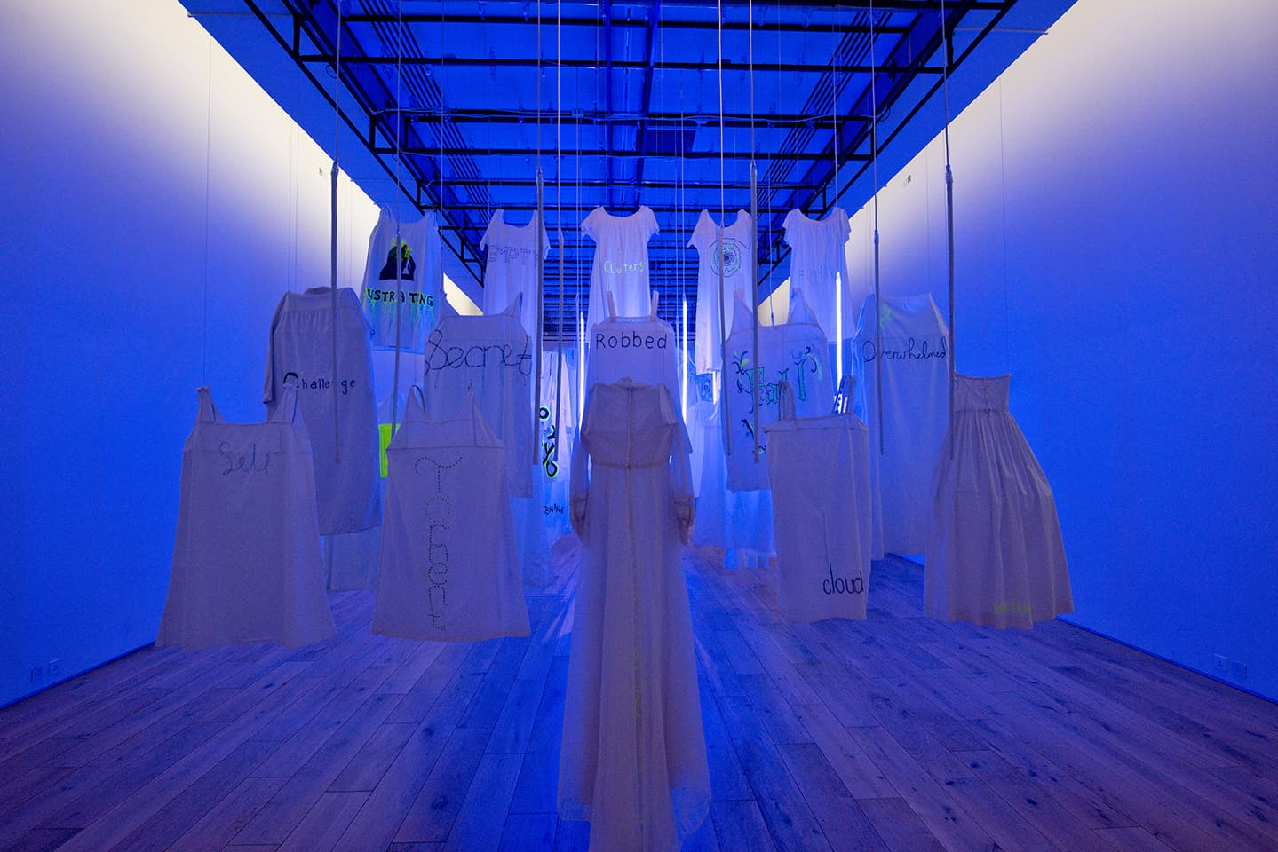 <strong>Out of the Blue</strong>, installation, from the back showing single word, with ultraviolet light, Susan Aldworth, 2020. Photograph by Colin Davison at Hatton Gallery.